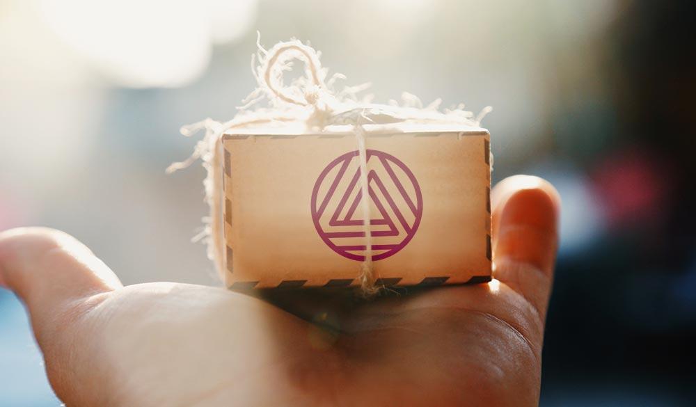 Mão estendida com uma mini-caixinha de madeira com o logo da Infinite Cloud Computing