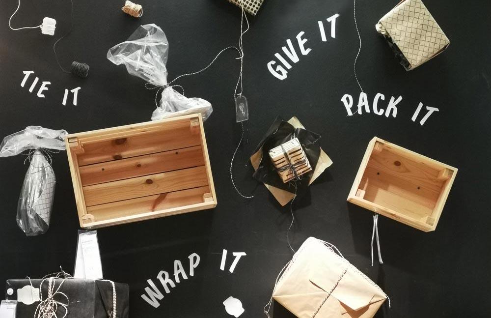 """Diversas caixas e pacotes sobre um fundo preto, com as frases """"wrap it"""", """"give it"""" e """"pack it"""""""