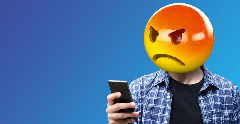 Homem com cara de emoji nervoso olhando para seu celular